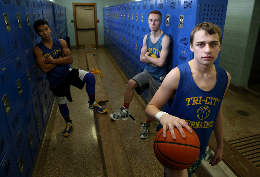 Tri-City High School basketball team member Dewie Gordon at front is shown in the school locker room before practice on Thursday, Jan. 21, 2016 along with two of his teammates who have given him additional support after his father recently drowned. At left back is Trever Martin and at middle is Devon Matthews. Gordon's mother died of cancer two years ago. David Spencer/The State Journal-Register