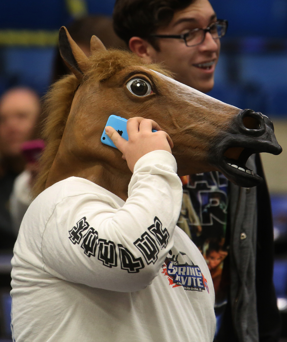 Southeast High School student Jared Smothers, who donned a horse mask, took a phone call during the game against Sacred Heart Griffin while standing in the Spartans student cheering section. The 68th annual City Boys Basketball Tournament kicked off on Thursday evening, Jan. 21, 2016 at Springfield's Prairie Capital Convention Center. David Spencer/The State Journal-Register