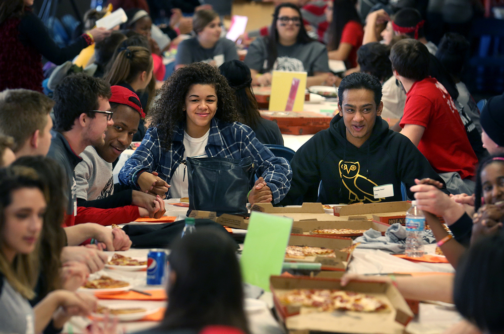 Roundtable moderator Jessica Freeman of Springfield High School clasps hands with fellow moderator Visakh Patel of SHS at right as well as with other city high school students before saying a short prayer before an early pizza dinner at the event. In 