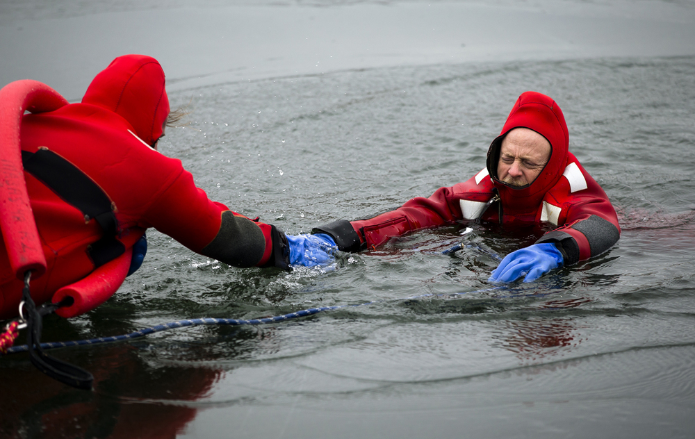 Captain Curt Moffitt, right, plays the victim as Driver Engineer Jake English approaches to rescue him from a hole cut out of the ice in the pond at Knights Action Park during the Springfield Fire Department's ice rescue training, Tuesday, Jan. 26, 2016, in Springfield, Ill. Justin L. Fowler/The State Journal-Register