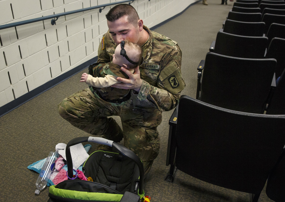 Illinois Army National Guard Spc. Jake Clements kisses his four-month-old daughter Charlotte before loading her into a car seat following a deployment ceremony for 30 soldiers at the Illinois Military Academy on Camp Lincoln in Springfield, Ill.. The 233rd Military Police Company will provide security operations in support of Operation Freedom's Sentinel, which is the new name for operations in Afghanistan. Ted Schurter/The State Journal-Register