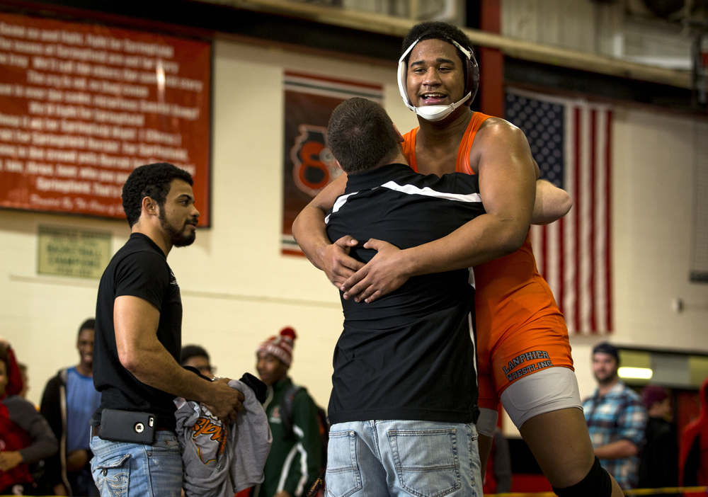 Lanphier's Edthao Crumb jumps into the arms of his coach after defeating Glenwood's Will Putnam in a 6-2 decision in the 285-pound championship match during the IHSA Class 2A Springfield Regional at Willard Duey Gymnasium, Saturday, Feb. 6, 2016, in Springfield, Ill. Justin L. Fowler/The State Journal-Register