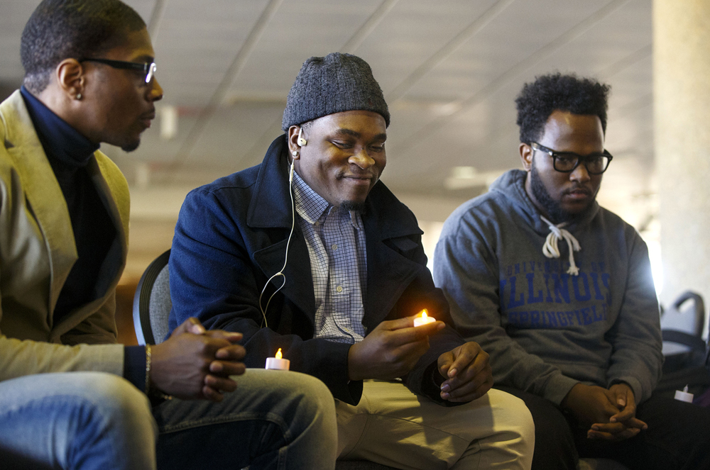 Malik Brown smiles as he turns on his electric candle during a Black History Month candlelight vigil  at the University of Illinois Springfield Monday, Feb. 1, 2016. Guests at the event were invited to share a remembrance of important people who had shaped their life.  Ted Schurter/The State Journal-Register