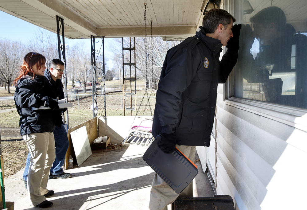 Donald Kauerauf with the Illinois Emergency Management Agency peers into the window of a flood-damaged home on Springfield Street during preliminary damage assessments in Kincaid Thursday, Feb. 4, 2016. Ted Schurter/The State Journal-Register