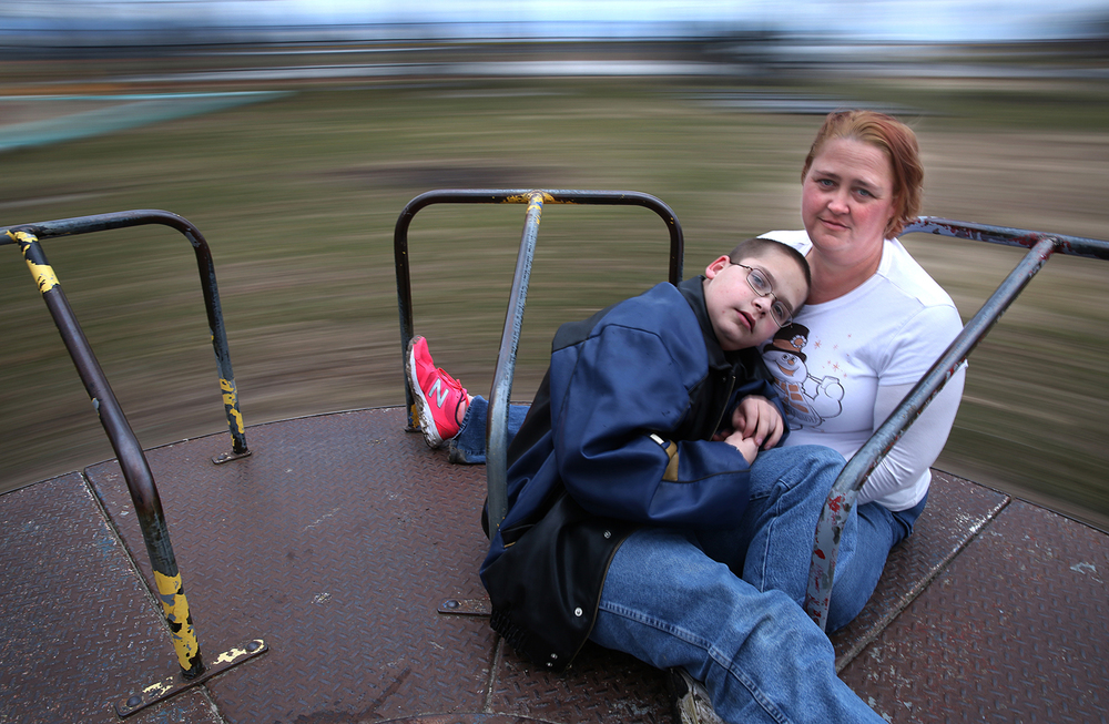 Veronica Morse, along with her autistic son Richard Tego, 14, an eighth-grader at Carlinville Middle School, take a ride on the merry-go-round at Raymond Park in Raymond on Thursday, Jan. 28, 2016. Cuts to autism services during the current state budget crisis have impacted Morse and her son. Spencer/The State Journal-Register
