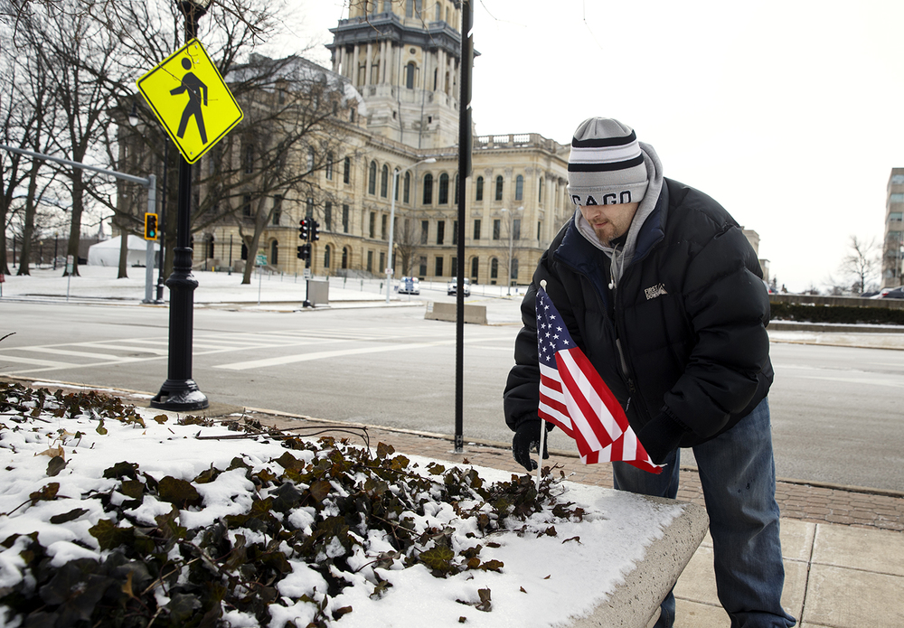 Jason Maggard plants a United States flag in the landscaping across from the capitol as he awaits the visit of President Barack Obama Wednesday, Feb. 10, 2016. Maggard, who was the first person to take a position outside the capitol, said he voted for the president in 2008 but is disappointed he hasn't lived up to his promises. Ted Schurter/The State Journal-Register