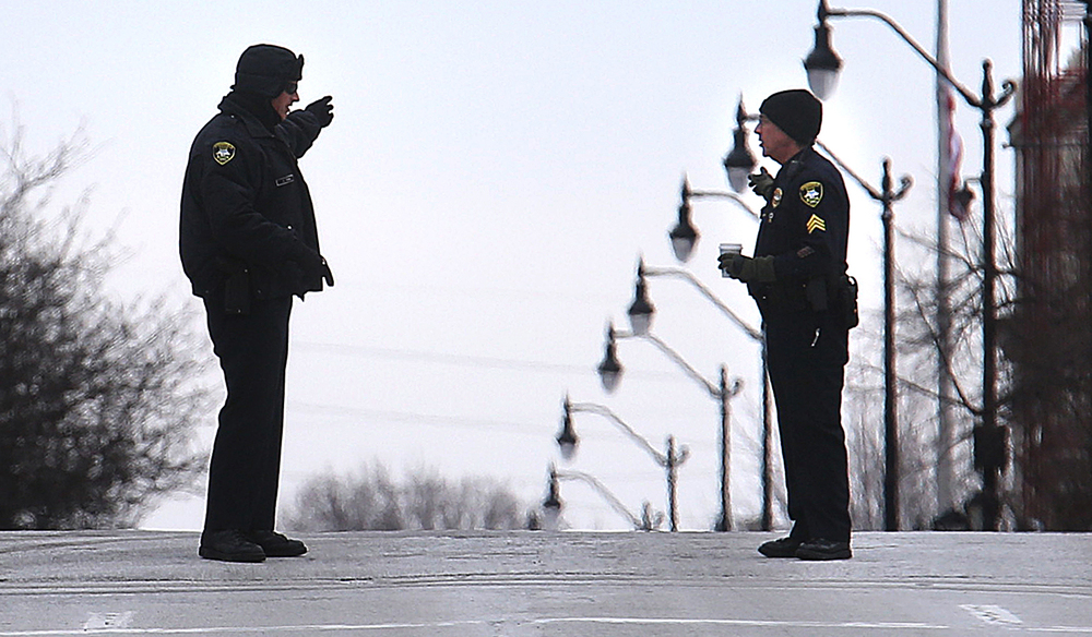 Two Springfield police officers talk with each other in the middle of Monroe St. near the State Capitol complex moments before President Barack Obama's motorcade passed through in route to the Illinois State Capitol in Springfield on Wednesday, Feb. 10, 2016. David Spencer/The State Journal Register