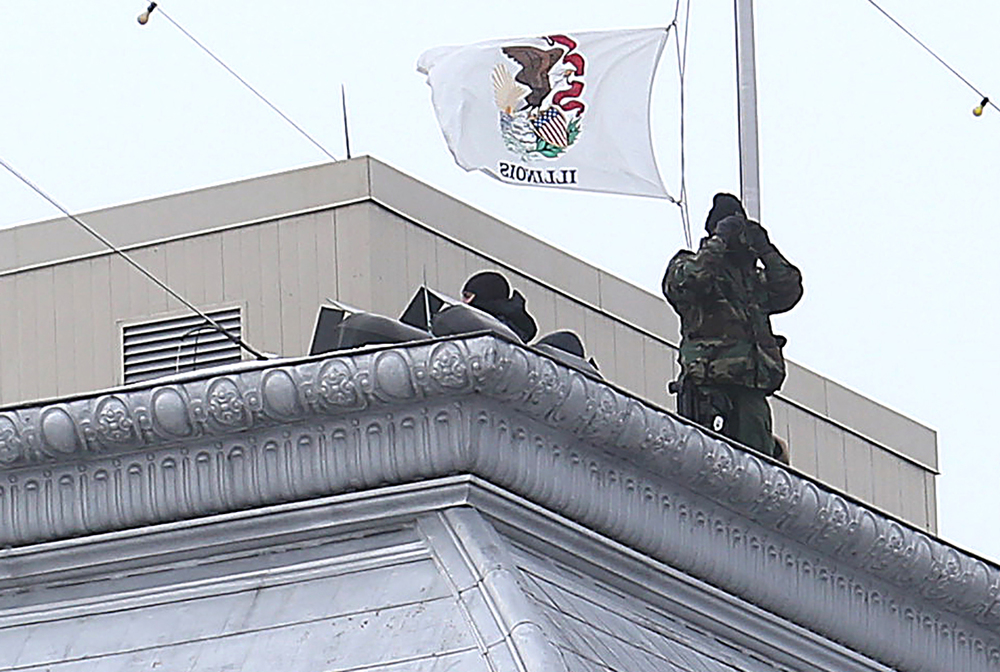 A security officer uses binoculars atop the Illinois State Capitol in Springfield on Wednesday, Feb. 10, 2016 before the arrival of President Barack Obama. David Spencer/The State Journal Register
