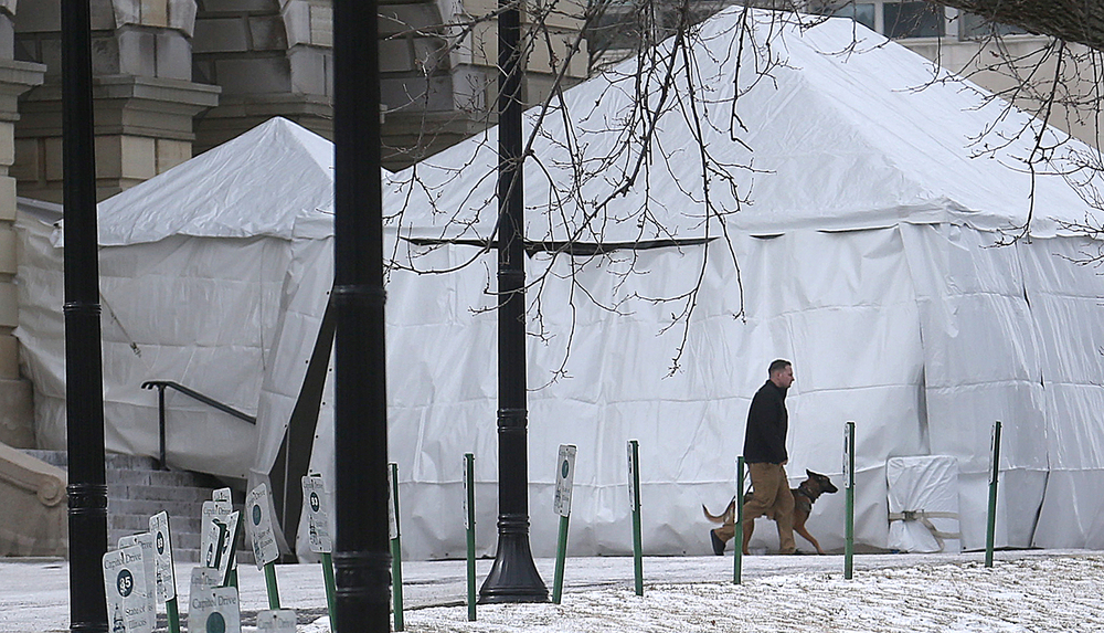 A security officer walks with a K-9 dog near a tent set up on the northside of the Illinois State Capitol in Springfield on Wednesday, Feb. 10, 2016 before the arrival of President Barack Obama. David Spencer/The State Journal Register