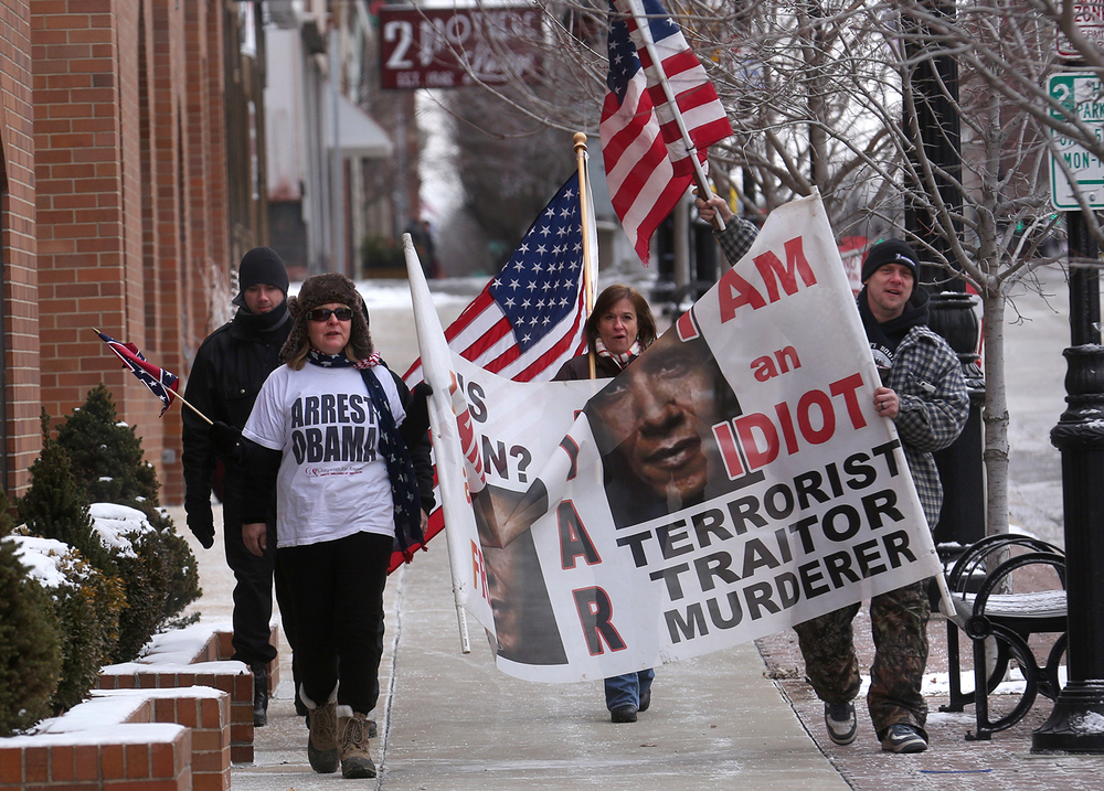 A group of people who stood opposed to the President's policies walk with signs towards the Illinois State Capitol on Wednesday, Feb. 10, 2016 before the arrival of President Barack Obama's motorcade. David Spencer/The State Journal Register