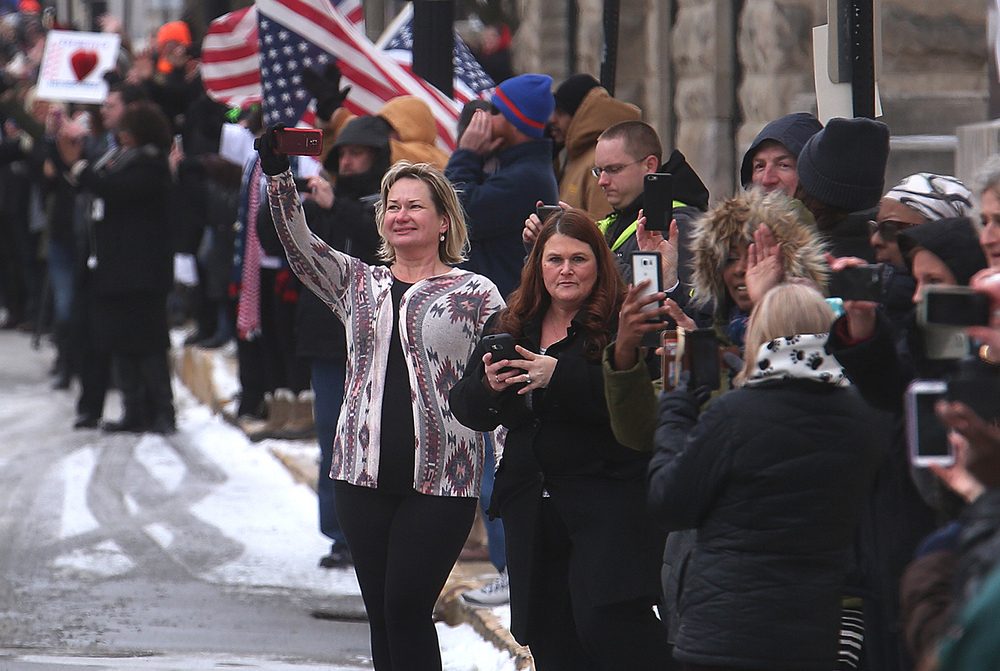 A group of people stood along Monroe St. across from the Illinois State Capitol on Wednesday, Feb. 10, 2016 and take pictures during the arrival of President Barack Obama's motorcade. David Spencer/The State Journal Register