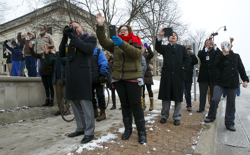 Spectators record and wave to the passing presidential motorcade as it turns onto Capitol Avenue after President Barack Obama's address to the legislature Wednesday, Feb. 10, 2016. Ted Schurter/The State Journal-Register