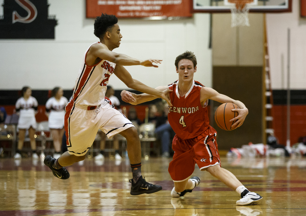 Glenwood's Matt Bahlmann (4) tries to reverse direction against Springfield's Keon Day (12) as he moves the ball across mid-court in the first quarter at Willard Duey Gymnasium, Friday, Feb. 12, 2016, in Springfield, Ill. Justin L. Fowler/The State Journal-Register