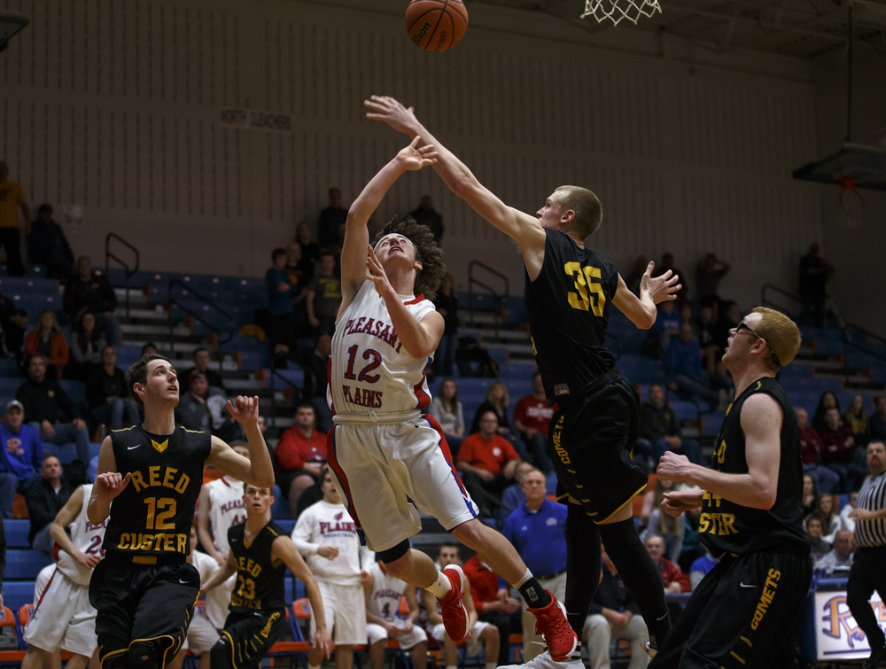 Pleasant Plains' Daulton Nibbe (12) puts up a shot against Reed-Custer's Brent Headrick (35) to send the game into overtime in the fourth quarter during the Riverton Subway Shootout at Riverton High School, Saturday, Feb. 13, 2016, in Riverton, Ill. Justin L. Fowler/The State Journal-Register