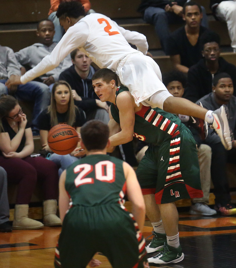 Lincoln's Isaiah Bowers tries to get the ball to a teammate as Lanphier defender Cardell McGee ends up on Bower's back during first half action. David Spencer/The State Journal Register