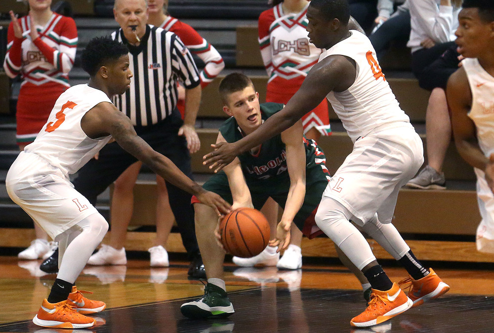 Lincoln's Ben Grunder is trapped by Lanphier defenders Zavier Bishop at left and Corrington Jones. David Spencer/The State Journal Register
