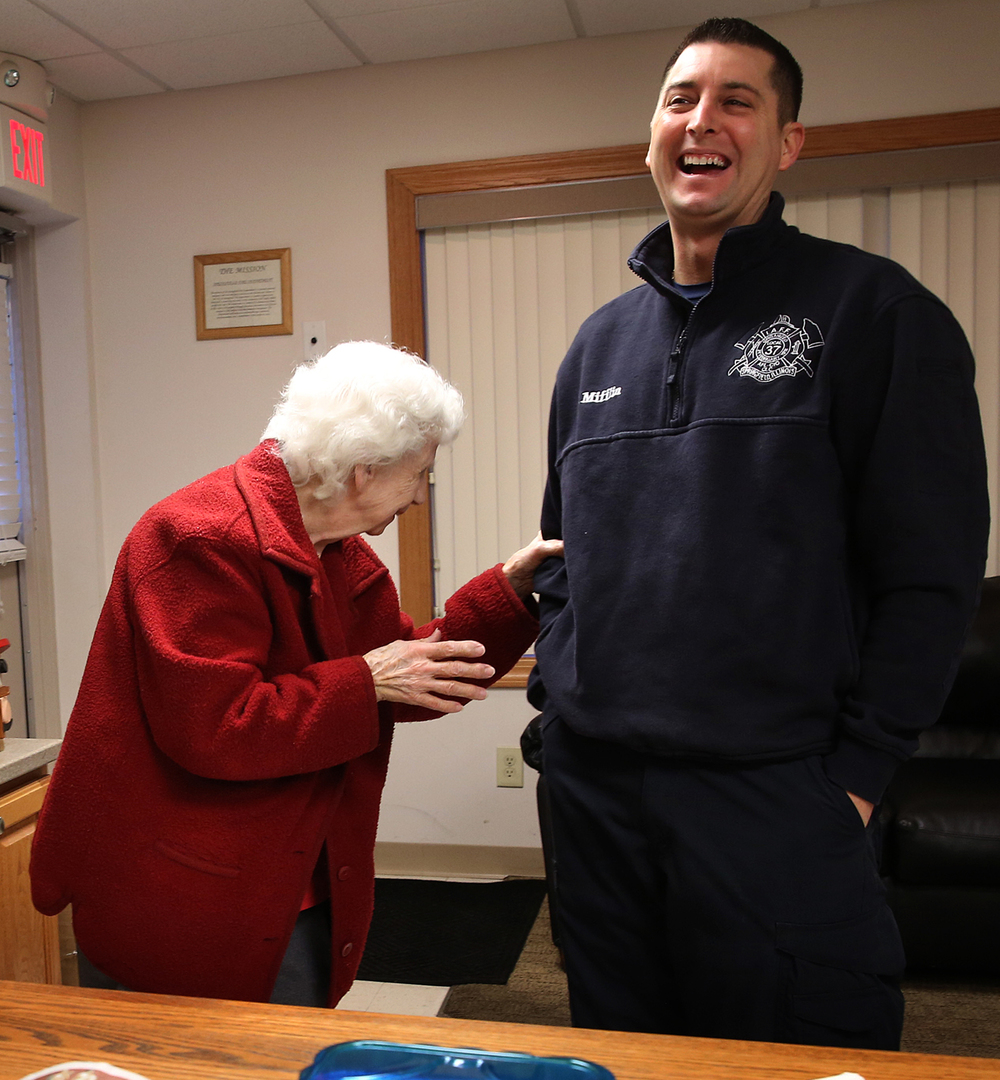 Barbara Mundhenke has a laugh with Springfield firefighter Josh Mifflin after making an early morning delivery of German Chocolate cake to Springfield fire station #8 on W. Monroe St. on Saturday morning, Feb. 20, 2016.  Barbara Mundhenke, 83, was recently made an honorary member of Springfield's Associated Fire Fighters of Illinois Local 37 for her efforts over the past seven year in baking cakes and delivering them to Springfield fire stations. David Spencer/The State Journal Register