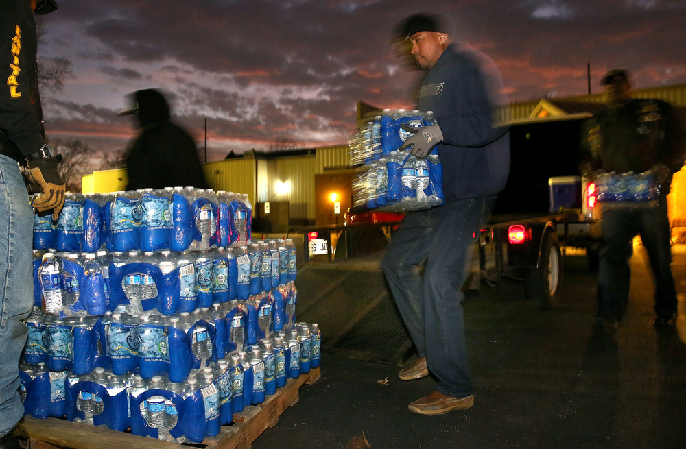 Tony Hubbard and other members of Springfield's Capital Cruisers Motorcycle Club stack cases of bottled water in the parking lot of Union Baptist Church Thursday, Feb. 18, 2016. The Church coordinated a two-day collection of water for the citizens of Flint, Mich. David Spencer/The State Journal Register