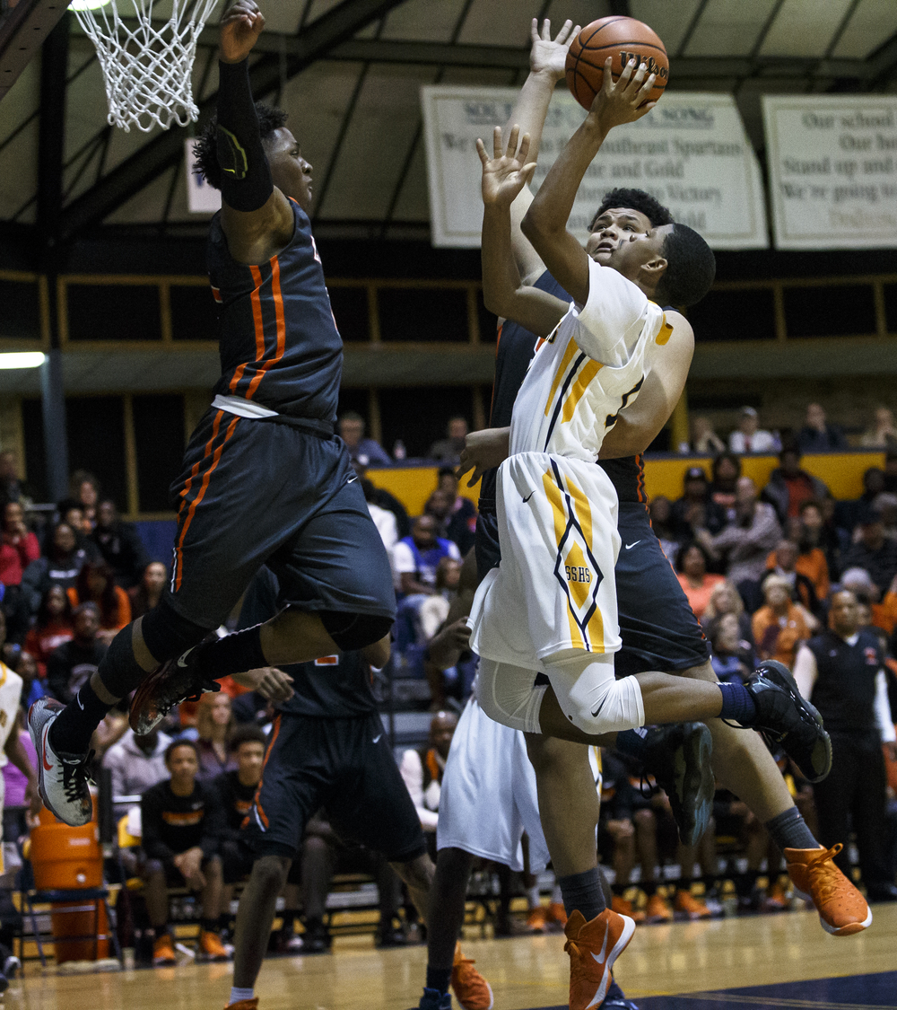 Southeast's Trevyon Williams (14) goes up to the basket against Lanphier's Yaakema Rose (1) and William Boles (50) in the first half at Herb Scheffler Gymnasium, Friday, Feb. 26, 2016, in Springfield, Ill. Justin L. Fowler/The State Journal-Register
