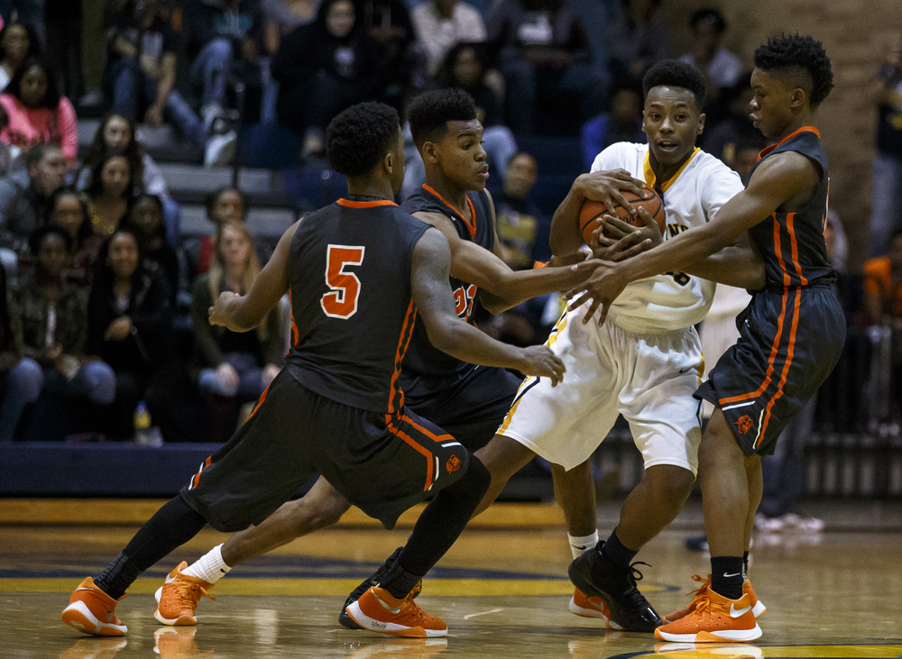 Southeast's Mark Johnson (33) is surrounded by a trio of Lanphier defenders as the Lions try to force a turnover in the second half at Herb Scheffler Gymnasium, Friday, Feb. 26, 2016, in Springfield, Ill. Justin L. Fowler/The State Journal-Register