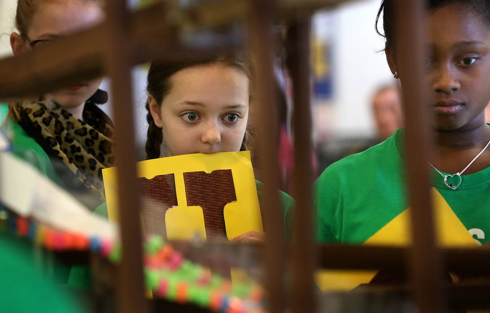 Owen Marsh fifth grade students Sadie Brillhart at center and Gianna Byars watch closely as a mining cart makes its way down a section of track at bottom of frame as part of a team competing with a gold mining themed Rube Goldberg machine Saturday morning. David Spencer/The State Journal Register