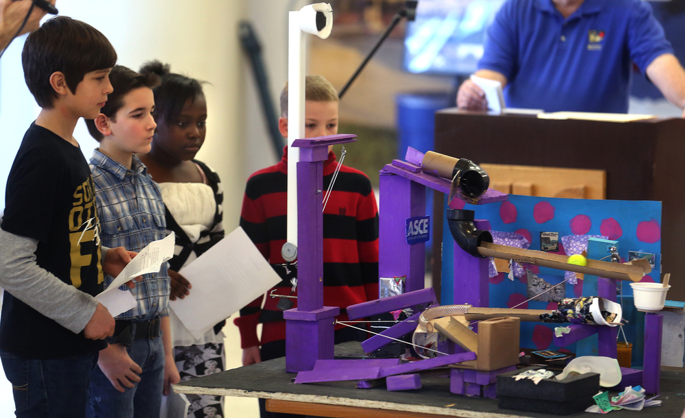 A team of Dubois Elementary fifth grade students watch as a fluorescent golf ball makes its way down a track after their Messy Room-themed Rube Goldberg machine was set in motion for the judges Saturday. David Spencer/The State Journal Register
