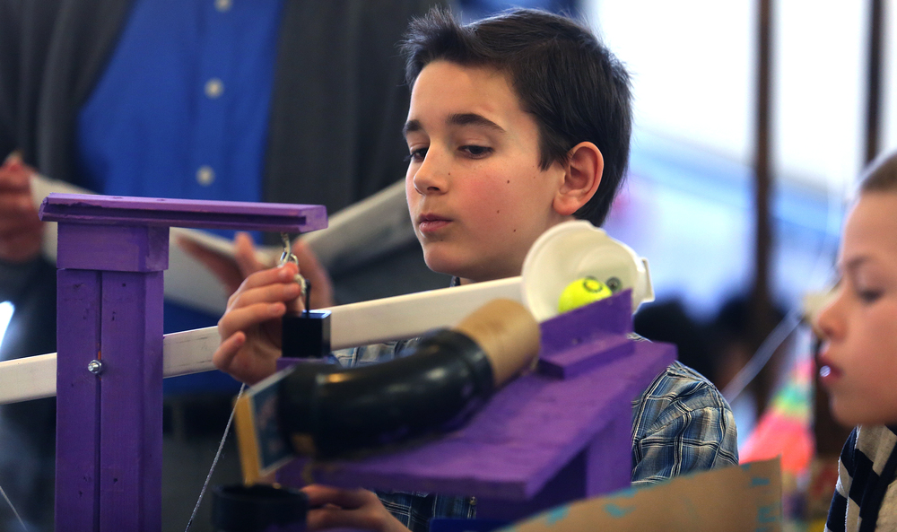 Dubois Elementary fifth grade student Alexander Boucher adjusts a pulley before his team's Messy Room-themed Rube Goldberg machine was set in motion for the judges Saturday. David Spencer/The State Journal Register