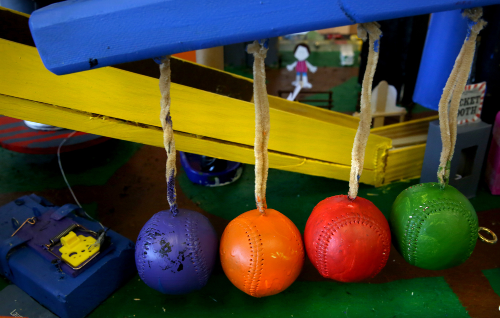 A series of baseballs, each painted a different color, would eventually be set into motion which would spring a mouse trap at left: part of Our Savior Lutheran School's funhouse arcade-themed Rube Goldberg machine built by a team of fifth grade students from the school, on display in the Student Union at LLCC Saturday. David Spencer/The State Journal Register