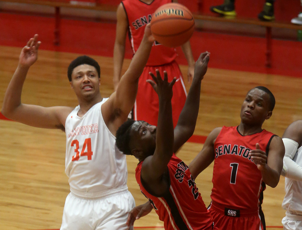 Springfield player Justin Pettis tries to grab a rebound while Lanphier player Davon Higgerson-Harris gets a hand on it. David Spencer/The State Journal Register