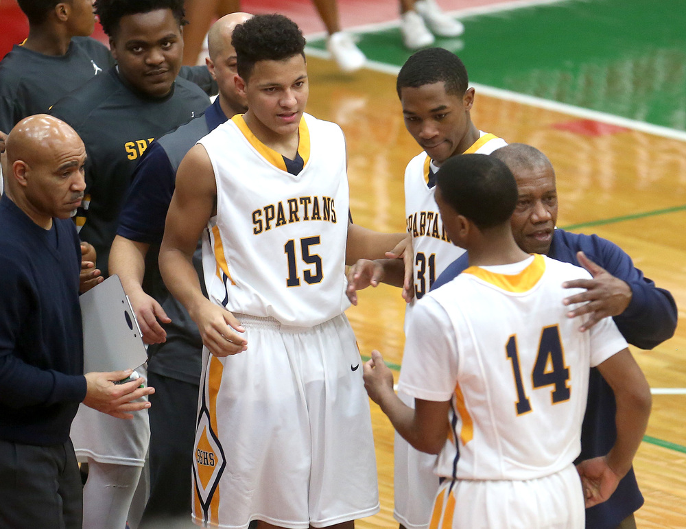 Southeast head coach Lawrence Thomas at right greets Trevyon Williams (#14) while teammates Jordan Stapleton (#15) and Kobe Medley (#31) prepares to greet Williams at the conclusion of the game.  David Spencer/The State Journal Register