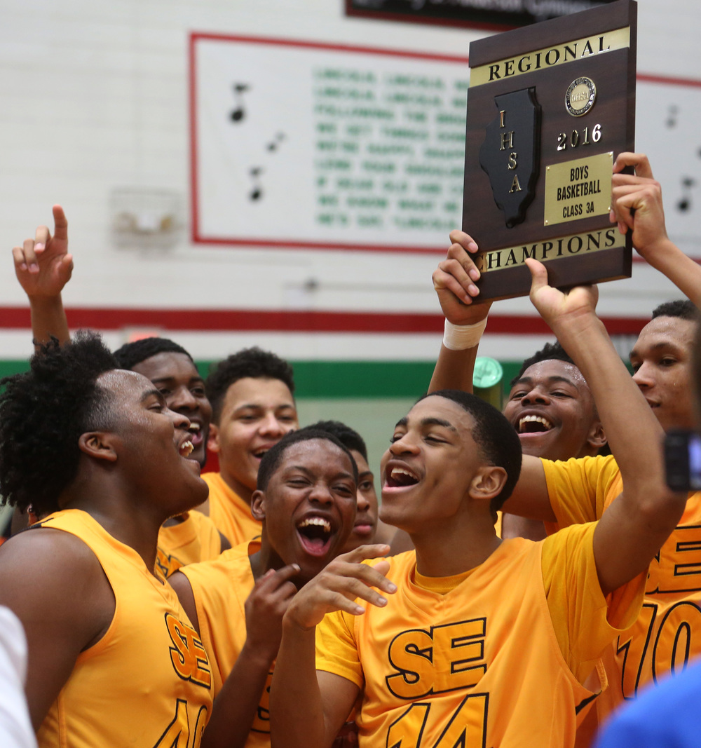Southeast players celebrate with the championship plaque after defeating Eisenhower Friday night in Lincoln.  David Spencer/The State Journal Register