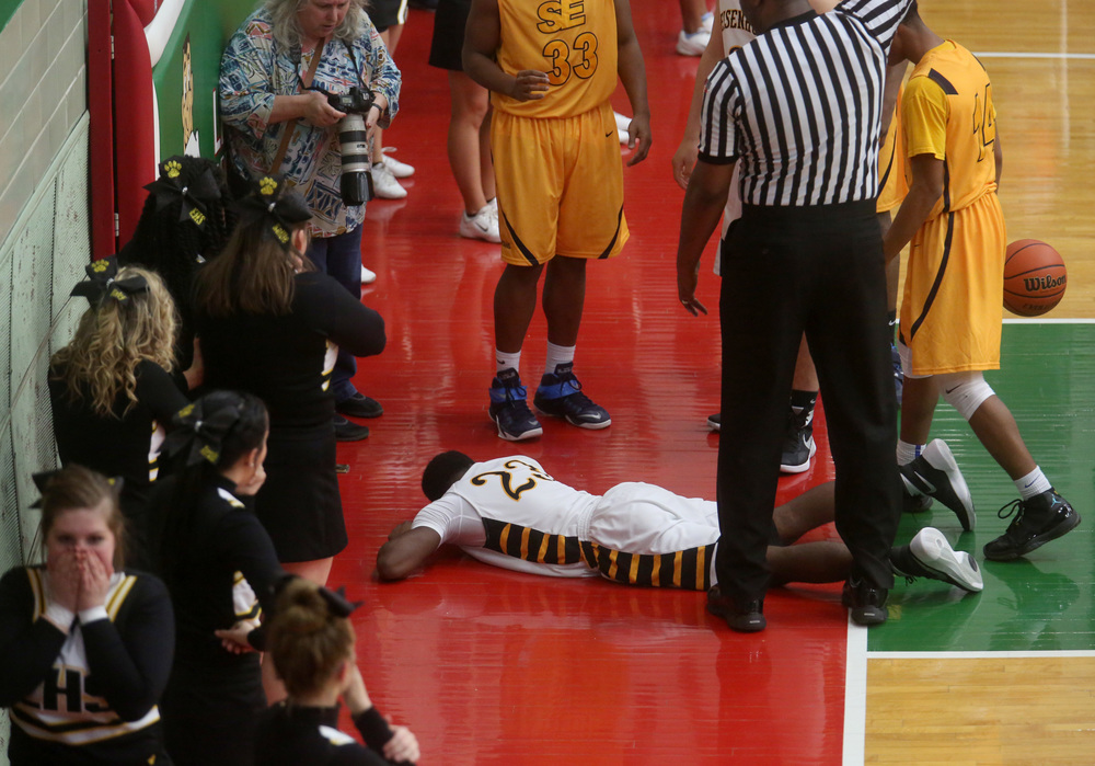 Eisenhower player Qualyn Young landed on the floor hard while trying to put up a shot during the second half. He walked while escorted off the court with the help of a coach. David Spencer/The State Journal Register