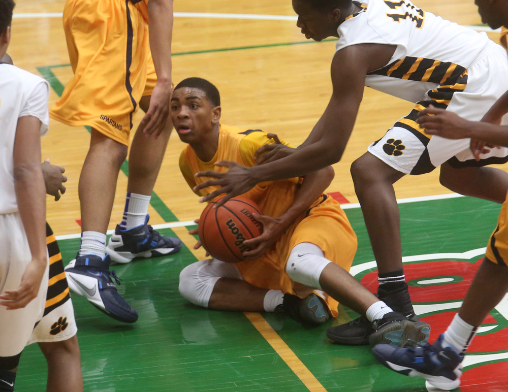 Southeast player Trevyon Williams tries to pass the ball while on the floor late in the game. David Spencer/The State Journal Register