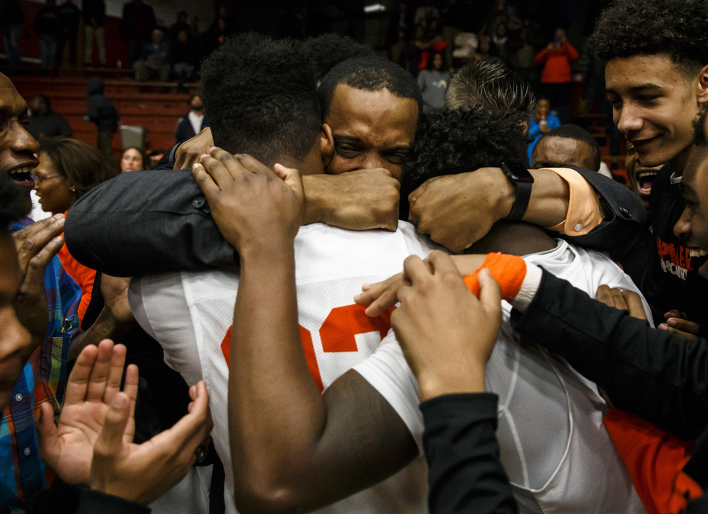 Lanphier head basketball coach Blake Turner is mobbed by his players after making his way to the court after the Lions 76-64 victory over Jacksonville in the Class 3A Jacksonville Regional championship game at the Jacksonville Bowl, Friday, March 4, 2016, in Jacksonville, Ill. Justin L. Fowler/The State Journal-Register