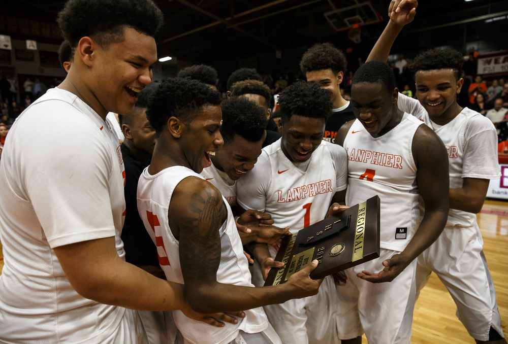 Lanphier's Xavier Bishop (5) and the Lions celebrate with the trophy after defeating Jacksonville 76-64 in the Class 3A Jacksonville Regional championship game at the Jacksonville Bowl, Friday, March 4, 2016, in Jacksonville, Ill. Justin L. Fowler/The State Journal-Register