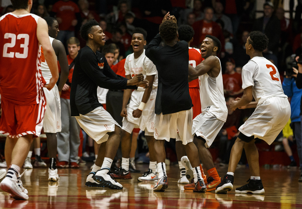 The Lanphier Lions begin to celebrate their 76-64 victory over Jacksonville in the Class 3A Jacksonville Regional championship game at the Jacksonville Bowl, Friday, March 4, 2016, in Jacksonville, Ill. Justin L. Fowler/The State Journal-Register