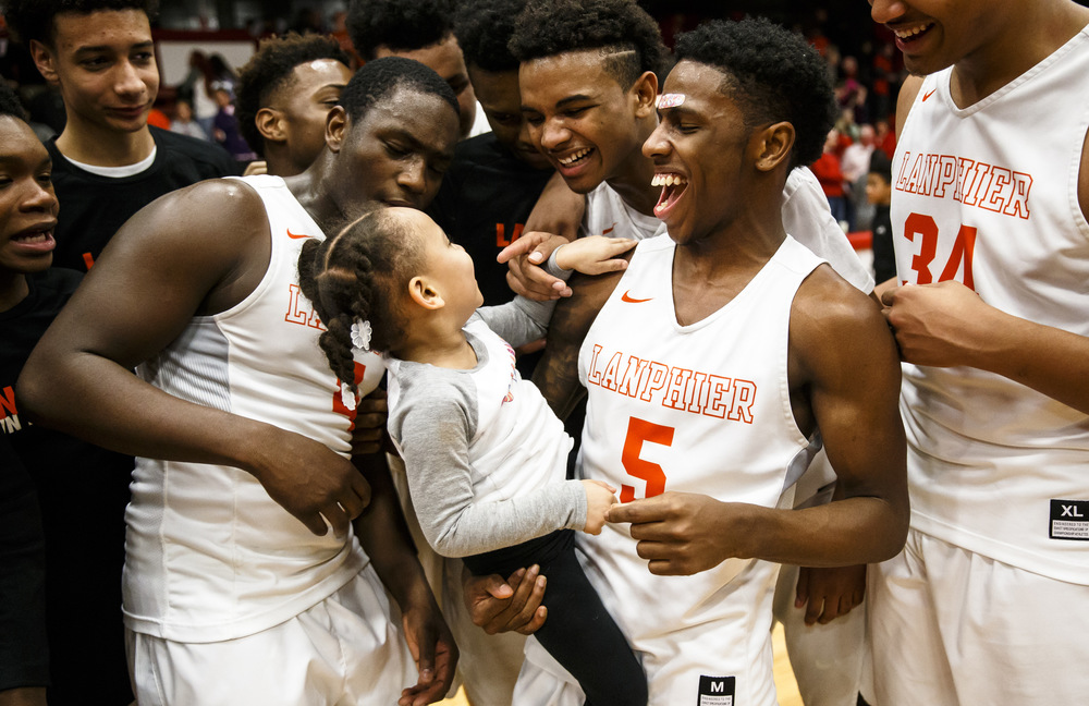 Lanphier's Xavier Bishop (5) holds Lanphier head basketball coach Blake Turner's daughter, Olivia, as the Lions celebrate their 76-64 victory over Jacksonville in the Class 3A Jacksonville Regional championship game at the Jacksonville Bowl, Friday, March 4, 2016, in Jacksonville, Ill. Justin L. Fowler/The State Journal-Register