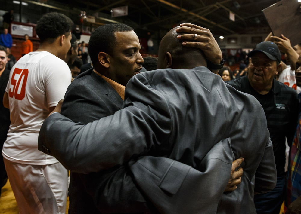 Lanphier head basketball coach Blake Turner hugs acting head coach Felipe Phillips after he made his way to the court to celebrate the Lions 76-64 victory over Jacksonville in the Class 3A Jacksonville Regional championship game at the Jacksonville Bowl, Friday, March 4, 2016, in Jacksonville, Ill. Justin L. Fowler/The State Journal-Register