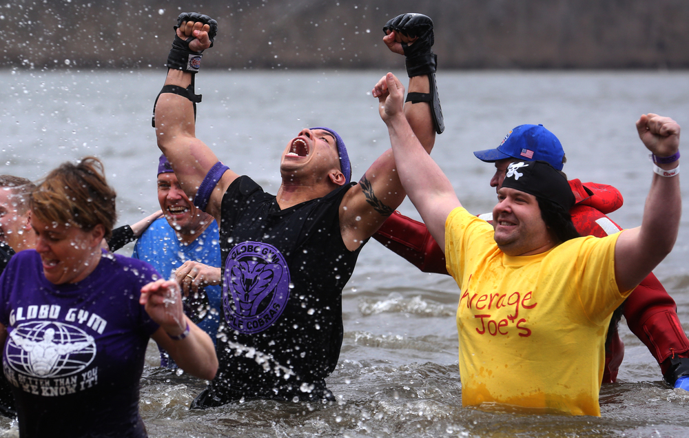 "Polar Plunge teams Globo-Gym at left and Average Joe's-rivals based on the movie DodgeBall- show off their inner ""Rocky"" while heading back to dry land Saturday afternoon. David Spencer/The State Journal Register"