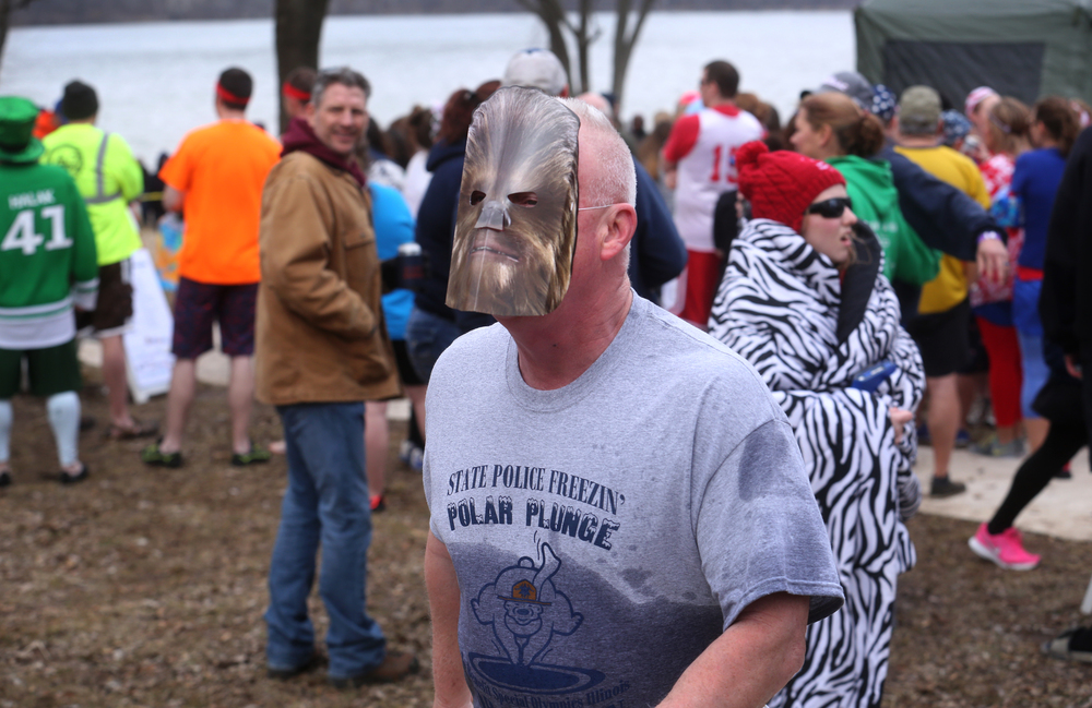 Wearing a Wookiee mask from the movie Star Wars, a plungers from the Illinois State Police Polar Plunge team quickly heads to the changing tent moments after exiting Lake Springfield. David Spencer/The State Journal Register