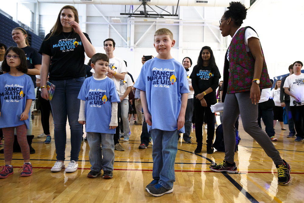 Brandon Mcilroy, 12, center, gets ready to start dancing along with his brother, Chandler Carroll, 7, left, as they watch a dance routine during the Dance Marathon at UIS fundraiser for the Children's Miracle Network at HSHS St. John's Children's Hospital at The Recreation and Athletic Center on the UIS campus, Friday, March 4, 2016, in Springfield, Ill. Mcilroy was one of the six local families who have benefited from the Children's Miracle Network that were participating in the event. Justin L. Fowler/The State Journal-Register