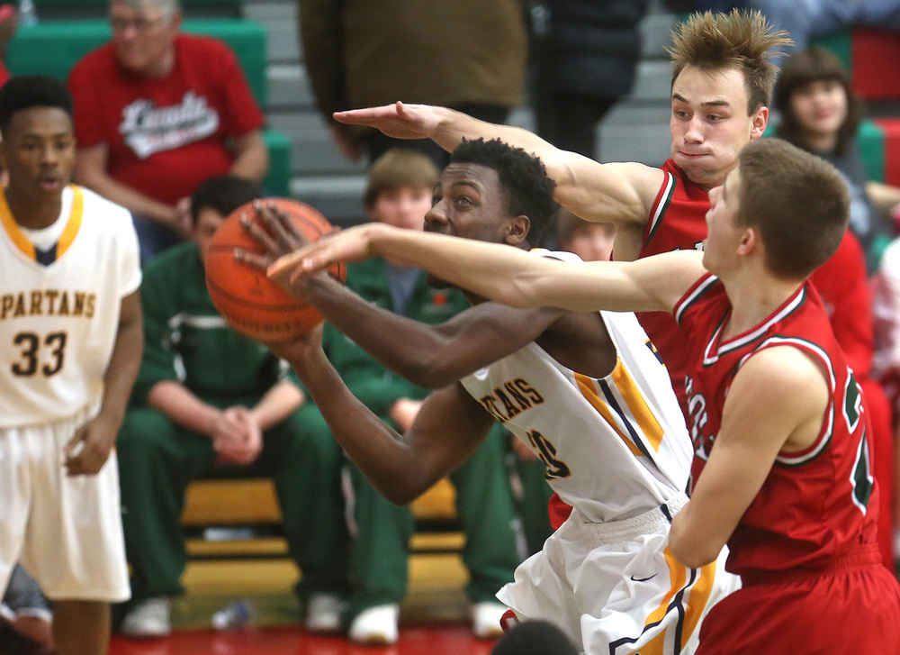Southeast player D'Angelo Hughes prepares to put up a shot in the first half while being covered by Lincoln Defenders Ben Grunder at front and Aron Hopp behind him. Southeast defeated Lincoln 43-35 in the semifinal game at the Class 3A boys Lincoln Regional at Lincoln's Roy S. Anderson Gym on Wednesday evening, March 2, 2016. David Spencer/The State Journal RegisterÊ