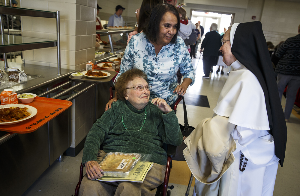 Rita Ryan, left, and her daughter, Theresa Flinn, visit with Sister Mary Dominic, right, as they pick up their meals in the dinning hall during Sacred Heart-Griffin's 57th Annual Mostaccioli Dinner at the SHG's West Campus, Sunday, March 6, 2016, in Springfield, Ill. Justin L. Fowler/The State Journal-Register