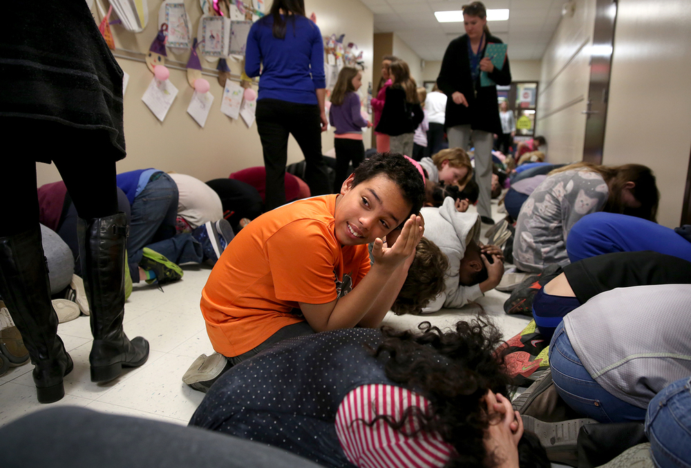 Fifth grade student Dean Thompson took a quick peek around him of his fellow students during the drill before he joined them in a croushing position on Thursday afternoon. Ridgely Elementary School in Springfield held its annual tornado drill on Thursday, March 3, 2016. Principal Ken Gilmore said the entire school took part from Pre-K to fifth grade, about 335 students in total. Mandated as part of the State of Illinois School Safety Drill Act, the drill Thursday was overseen by Springfield Fire Department firefighters based at the nearby Illinois State Fairgrounds. The five-minute drill involved students evacuating their classrooms and assembling in interior school hallways away from windows and glass doors where they assumed a duck and cover protective stance until the all-clear was sounded. David Spencer/The State Journal Register