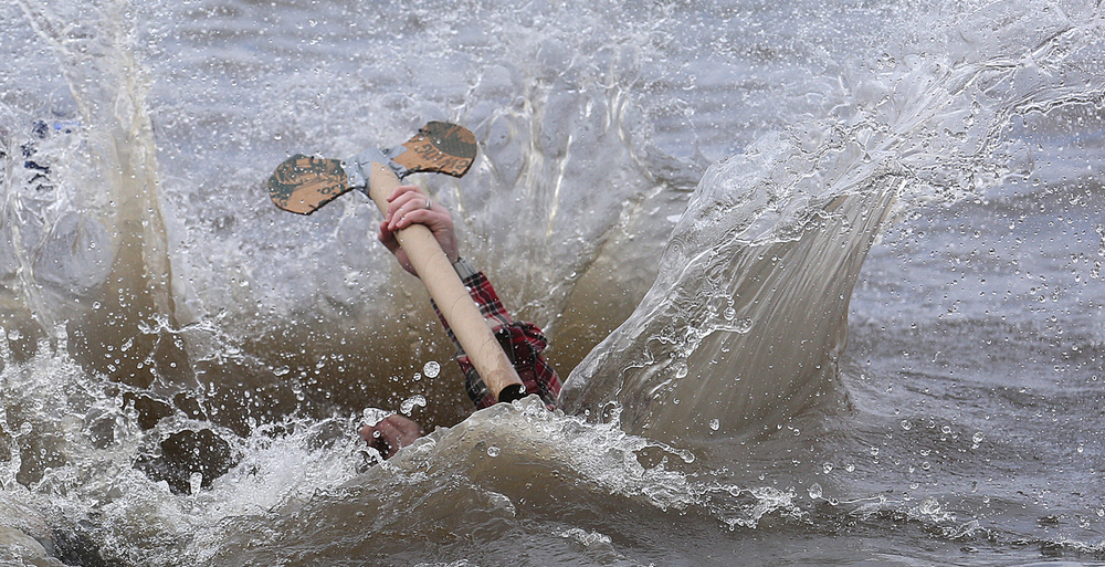 Paul Bunyan: aka: Cyrus Winnett of Springfield- seemed to be intent on keeping his cardboard axe dry while taking a deliberate submersive plunge into the frigid water on Saturday. The 2016 Law Enforcement Torch Run Polar Plunge to benefit Special Olympics Illinois took place in the frigid waters of Lake Springfield at the Knights of Columbus Hall #4179 in Chatham on Saturday, March 5, 2016. Through donations, the event supports Special Olympics programs in Illinois. Approximately 200 people took the plunge Saturday. David Spencer/The State Journal Register
