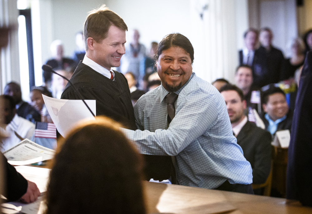 Fernando Benitez Ventura, center, shows his excitement as he receives his naturalization certificate from U.S. Magistrate Judge Eric Long during a naturalization ceremony at the Old State Capitol, Friday, Feb. 26, 2016, in Springfield, Ill. Justin L. Fowler/The State Journal-Register