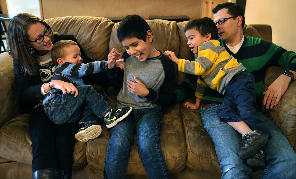 Nasko Newingham, 9, center, gets tickled by brothers Louis, 2 at left and Edward, 4 while seated with parents Ginger and Chance Newingham in the living room of his Athens home on Tuesday, Feb. 23, 2016. Ginger Newingham of Athens, a mom of two adopted special needs children from overseas, recently mounted a successful Internet campaign that forced Priceline to suspend their new TV advertisement which made a joke of one overseas adoption. That's because for her and husband Chance, it's personal. They know the heartache, stress and joy the experience really involves. David Spencer/The State Journal Register