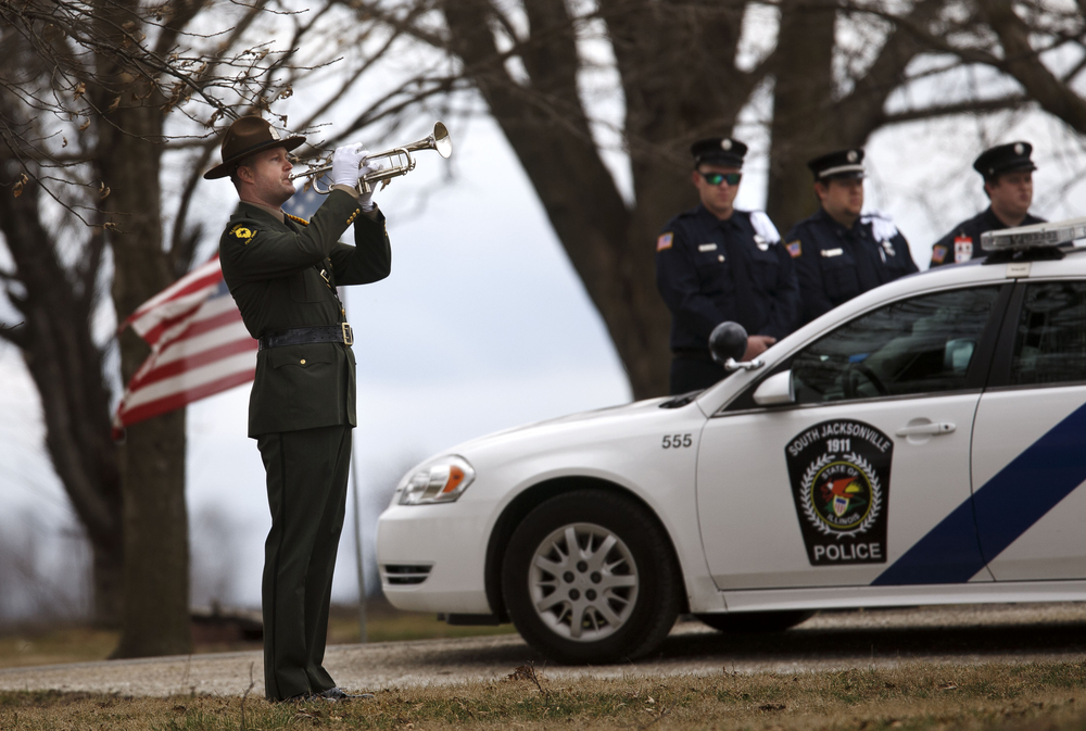 A member of the Illinois State Police Honor Guard plays Taps during graveside funeral services for South Jacksonville Police Officer Francis Scot Fitzgerald at the Murrayville Village Cemetery Wednesday, March 9, 2016. Officer Fitzgerald was killed in a car accident while on duty last week. Ted Schurter/The State Journal-Register