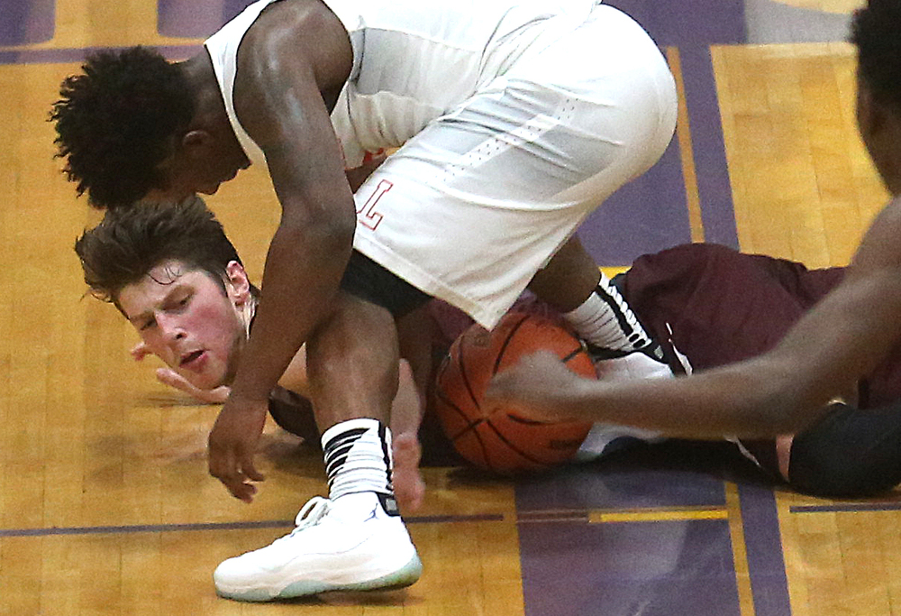 Lanphier's Yaakema Rose at front fights for a loose ball on the floor along with Champaign Central's Nick Finke. David Spencer/The State Journal Register