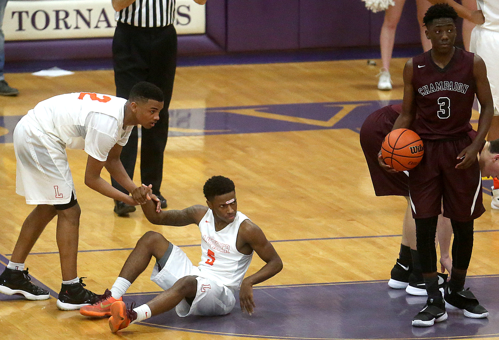 A collision between Lanphier's Xavier Bishop on floor and Champaign Central's Kamron Reaves at right brought Bishop to the free throw line.David Spencer/The State Journal Register